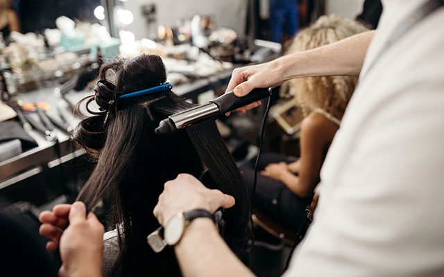 Hair stylist uses ghd curve to style model's hair.