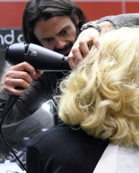 Stylist using ghd air to style hair.