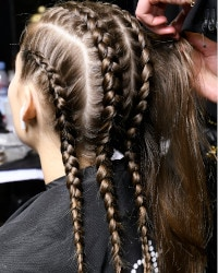 Model's hair styled with braids to fit under the wig.